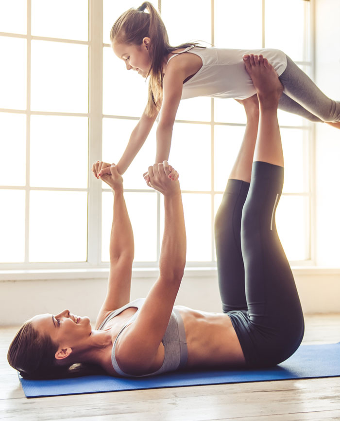 Woman doing yoga lifting her young child with her legs after hernia repair