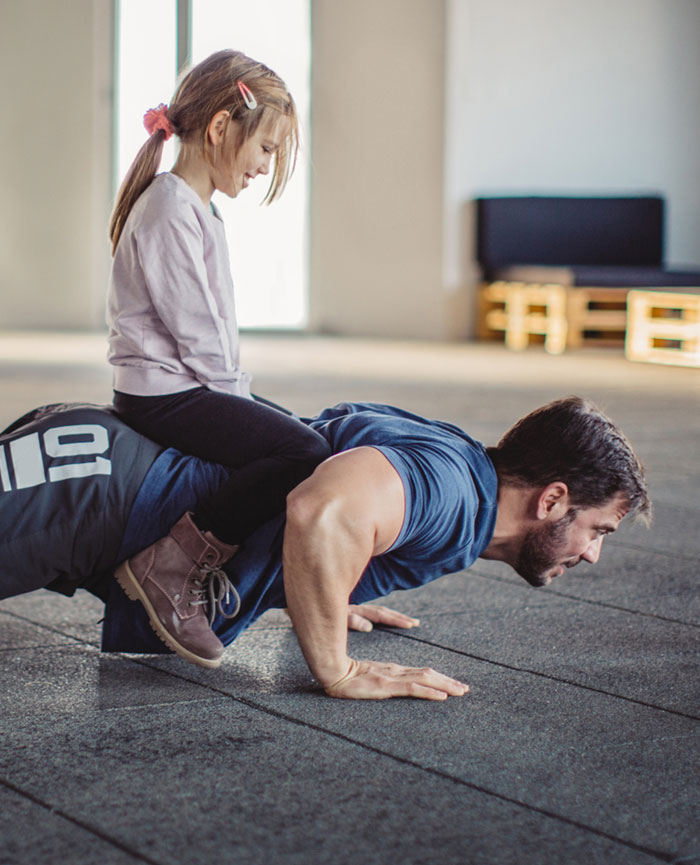 man doing push ups with child on his back after hernia surgery